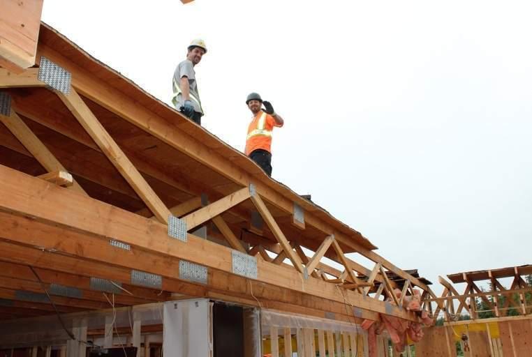 Matt Senciew and Yan-David Chamberland of k'awat'si Construction frame the roof at Kwa'lilas Hotel.