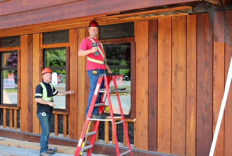 Ryan Handley and Steven Dugas work on the windows and siding of the conference centre.