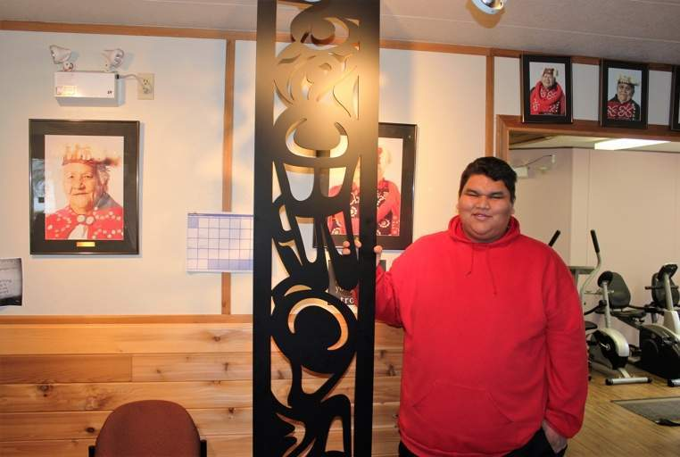 Walter Brown holds a room divider he designed and carved, which will be featured in all 85 rooms at Kwa'lilas Hotel.