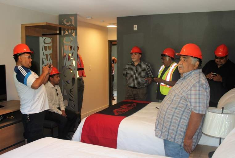 Chief and Council get a sneak peek of a staged room in Kwa'lilas Hotel, complete with artwork designed by local artists.